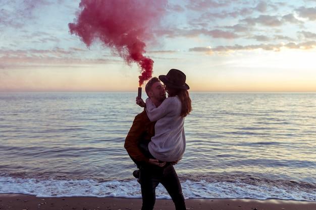 海の海岸に煙爆弾を持つ腕の中で女性を保持している男