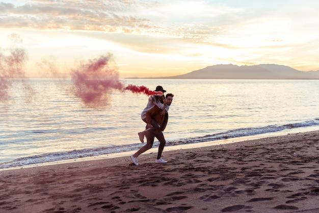 Мужчина держит женщину с дымовой шашкой на спине на берегу моря