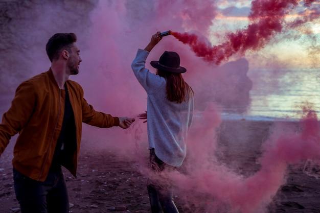カップルが海岸にピンクの煙爆弾を楽しんで