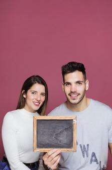 Молодая улыбающаяся леди и позитивный парень показывает фоторамку