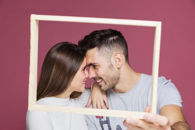 フォトフレームを示す肯定的な男の肩に手を持つ若い笑顔の女性