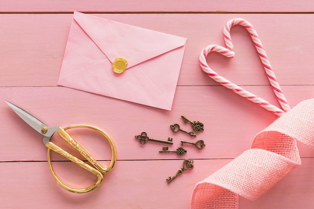 封筒、はさみ、キャンディーの杖の近くのキーのセット