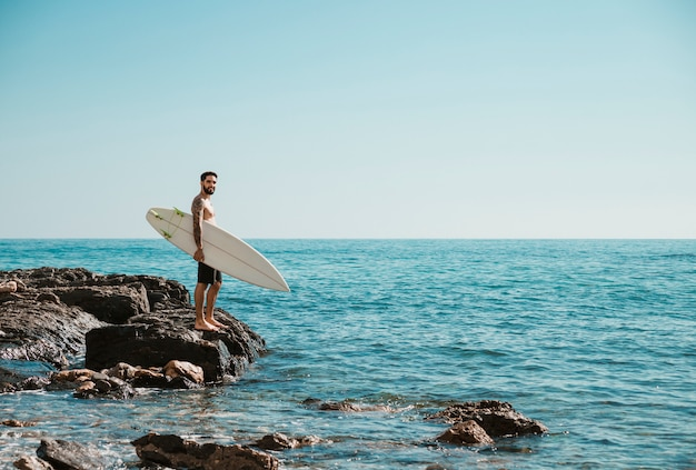 岩が多い海岸に立っている若いサーファー
