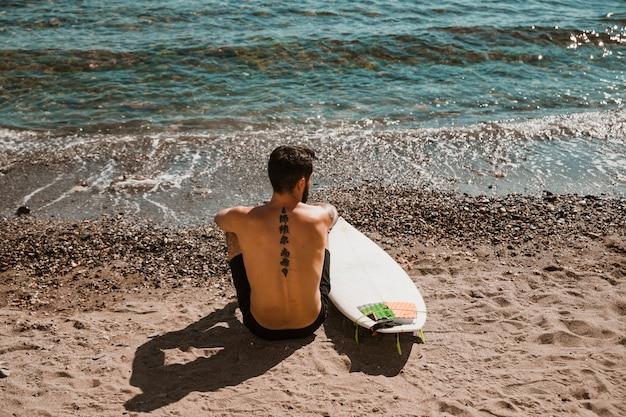 砂浜の上に座ってサーフボードを持つ匿名男