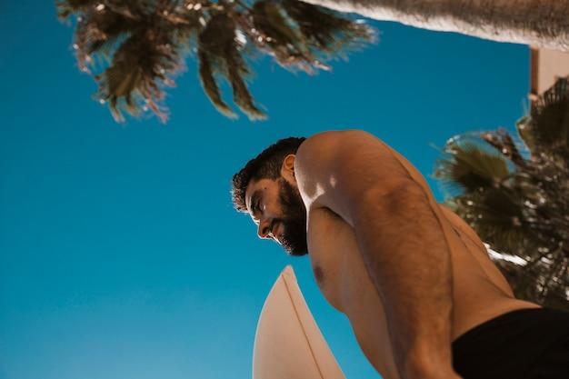 サーフボードを抱えた上半身裸の男