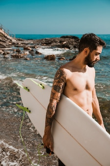 きれいな海の近くのサーフボードを持つハンサムな男