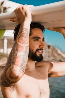 Молодой человек с доской для серфинга на голове на пляже
