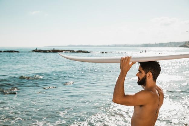 Молодой человек с доской для серфинга на голове на берегу возле воды