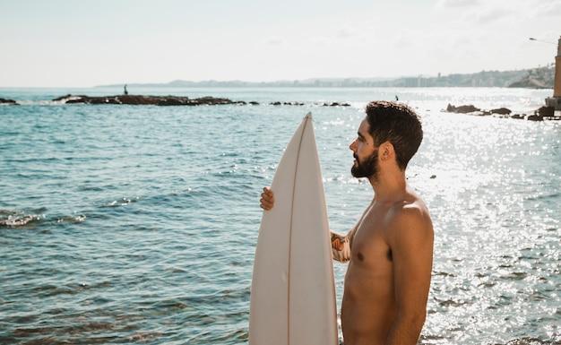Молодой человек с доской для серфинга на берегу возле воды