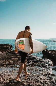 Молодой человек с доской для серфинга собирается на воду