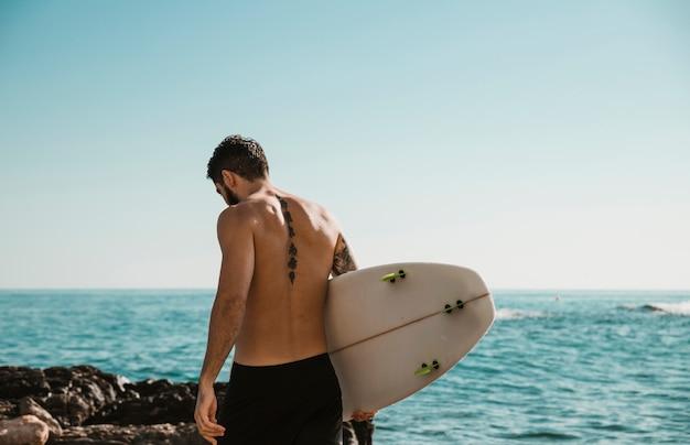 海の近くのサーフボードを持つ若い男