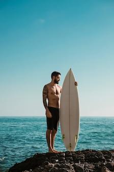 Человек без рубашки с доской для серфинга стоит на скале