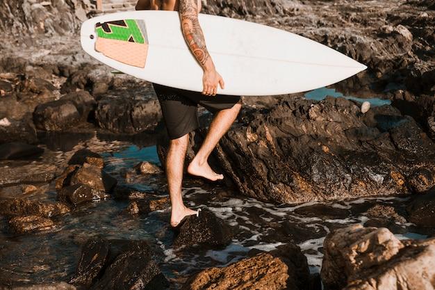 Человек идет по каменному пляжу с доской для серфинга у воды