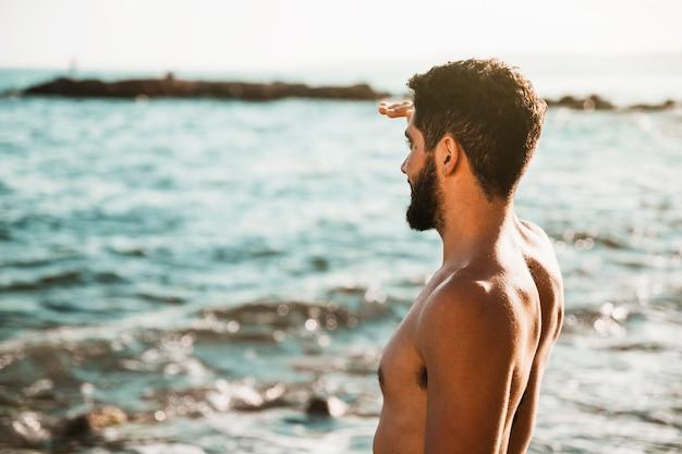 Молодой парень смотрит далеко от воды