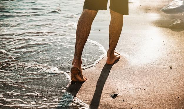 水の近くの海岸を歩く男の足