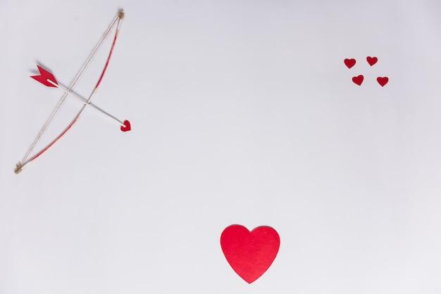 白いテーブルの上の弓と愛の矢印
