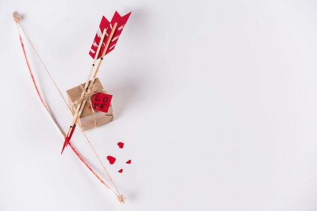 白いテーブルの上の弓とギフトボックスと愛の矢印