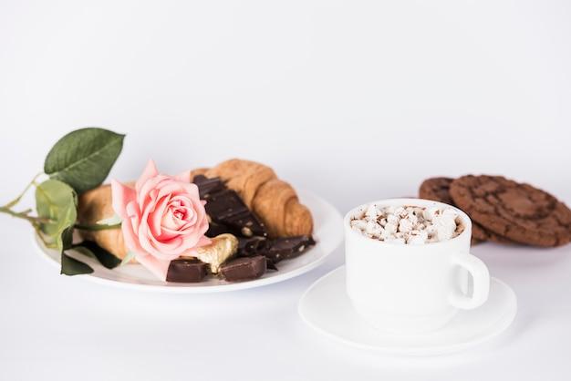 皿の上のバラの花とお菓子