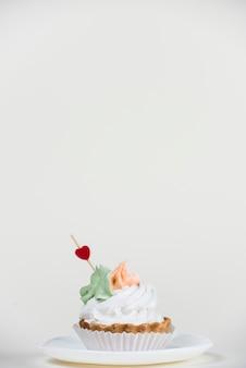 白いテーブルの上のカップケーキのハートトッパー