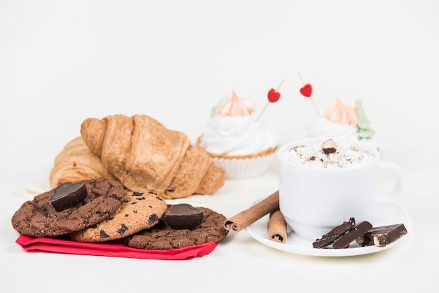 Разные сладости с чашкой кофе на столе