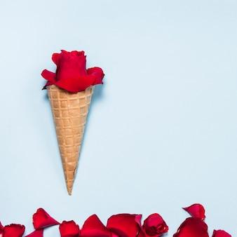 青いテーブルの上のワッフルコーンの赤いバラのつぼみ