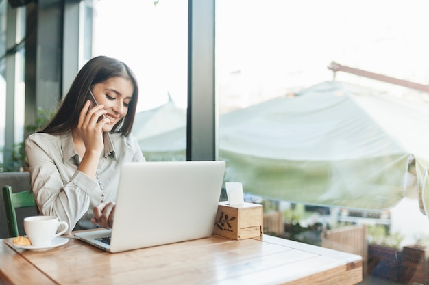Независимая женщина, работающая с ноутбуком в кафе