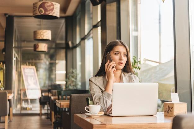 コーヒーショップでノートパソコンを扱うフリーランスの女性