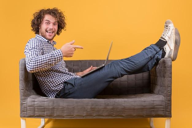 ソファの上のラップトップを持つ男