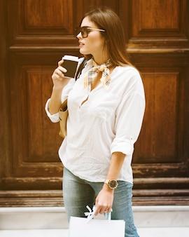 コーヒーを持っているショッピングガール