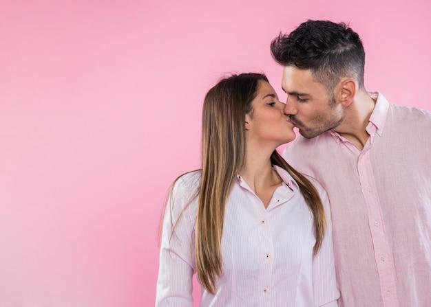 Молодая пара целуется на розовом фоне