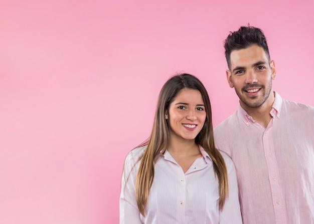 幸せなカップルのピンクの背景の上に立って