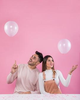 幸せなカップルの白い風船で遊ぶ