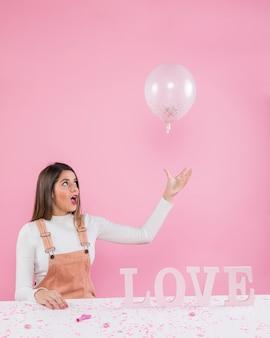 Женщина играет с воздушным шаром возле любовной надписи