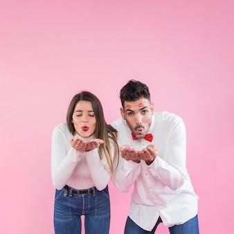 ピンクの背景にキスを吹いているカップル