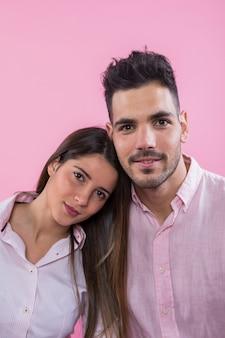 かわいいカップルのピンクの背景の上に立って