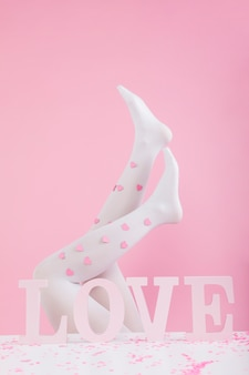 愛の碑文の近くの紙のハートとタイツの足