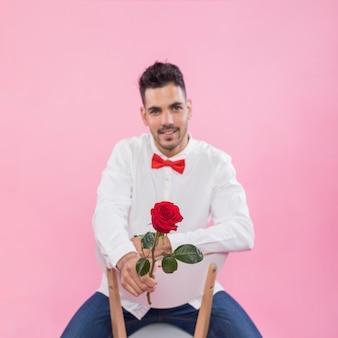 バラの椅子に座っている若い男