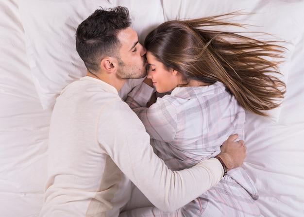 男がベッドの中でおでこに女性にキス