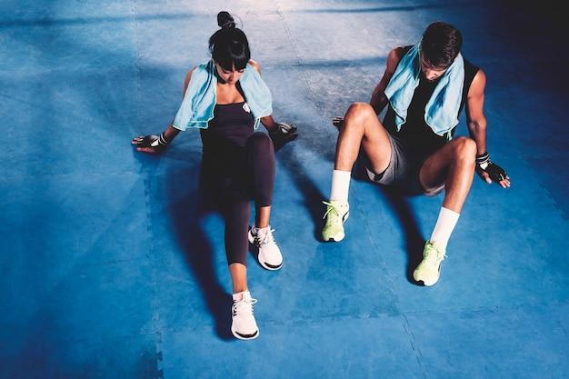 Вымотанная пара на полу в спортзале
