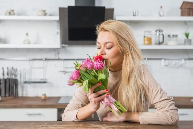 Женщина пахнущие свежие цветы на кухне