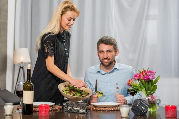 サラダのボウルを持つ女性の近くのテーブルに笑みを浮かべて男