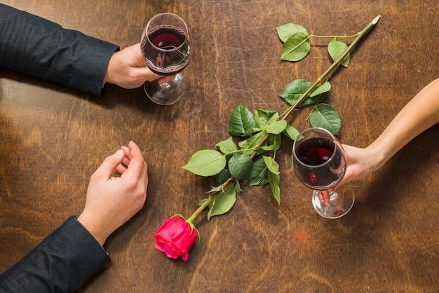メガネと花のテーブルで男と女の手