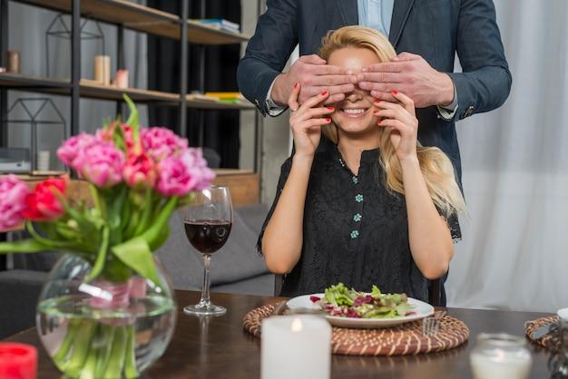 テーブルで陽気な女性に男性の目を閉じる