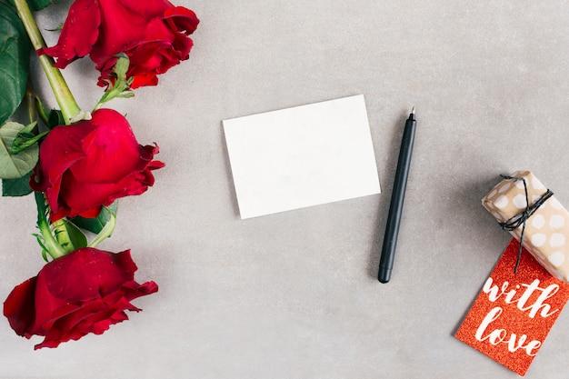 タグ、プレゼント、ペンと花の近くに紙