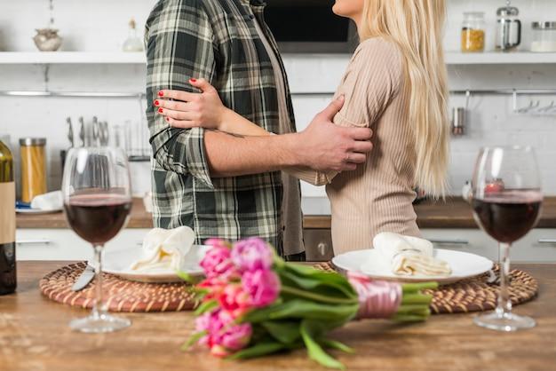 花とワインのグラスを持つテーブルの近くの女性と抱きしめる男