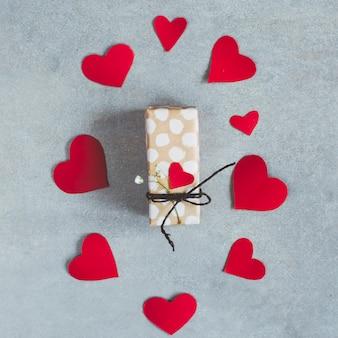 紙のハートのセットの間のプレゼントボックス