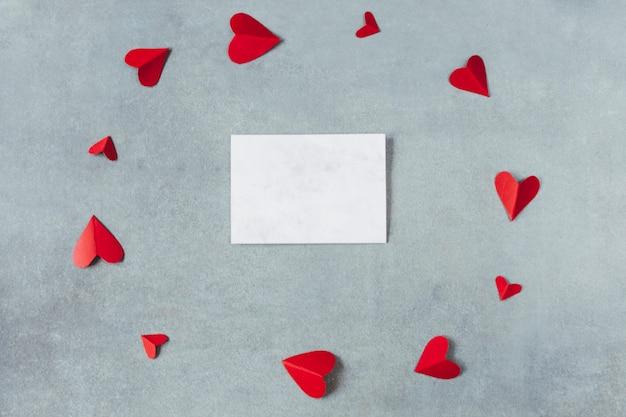 円の形でハートの赤い紙のシンボル間のシート