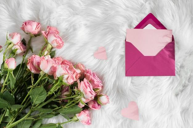 ウールの毛布の上の新鮮な花の近くの封筒