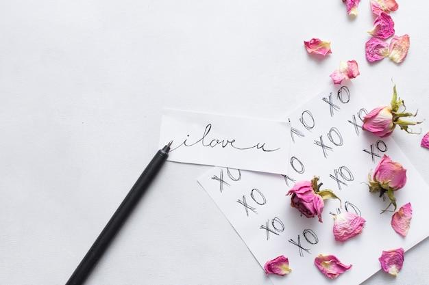 ペンと花のセットの近くのタイトルの紙
