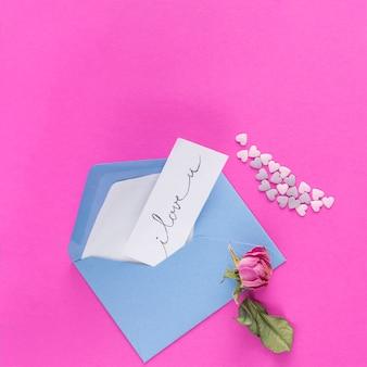 飾りの心と花の近くのタイトルの紙と封筒
